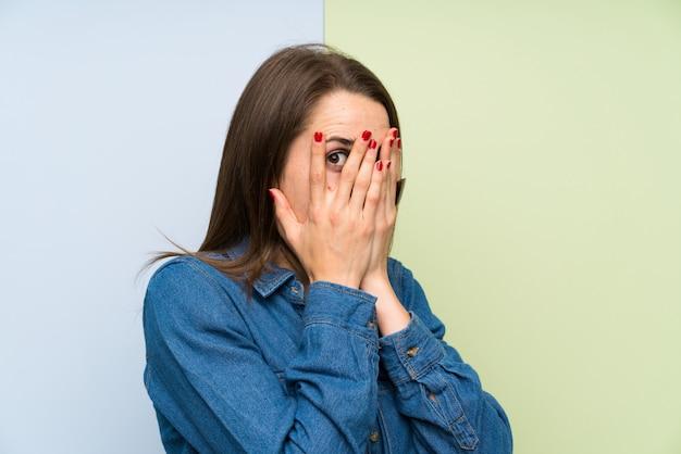 Młoda kobieta obejmujące oczy i patrząc przez palce