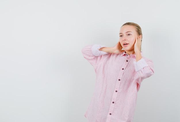 Młoda kobieta obejmujące uszy rękami w różowej koszuli i patrząc pozytywnie