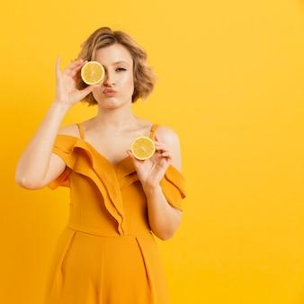 Młoda kobieta obejmujących oczy z plasterkami cytryny