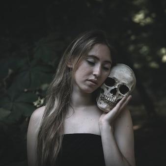 Młoda kobieta obejmuje czaszkę w drewnach