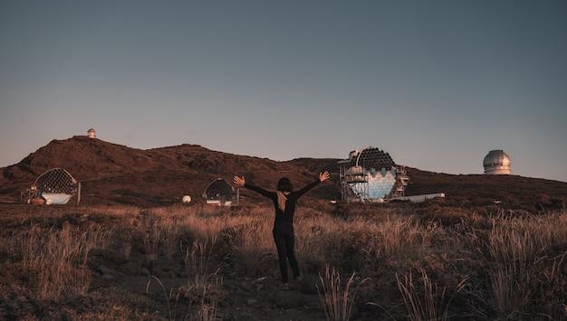 Młoda kobieta obok nowego obserwatorium astronomicznego caldera de taburiente o zachodzie słońca, la palma, wyspy kanaryjskie. hiszpania