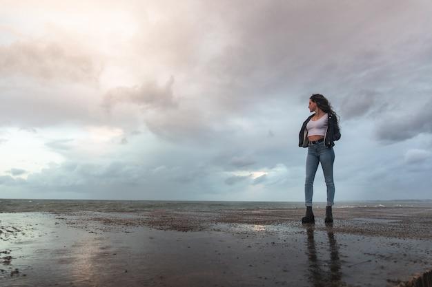 Młoda kobieta obserwująca, jak fale uderzają o skały.