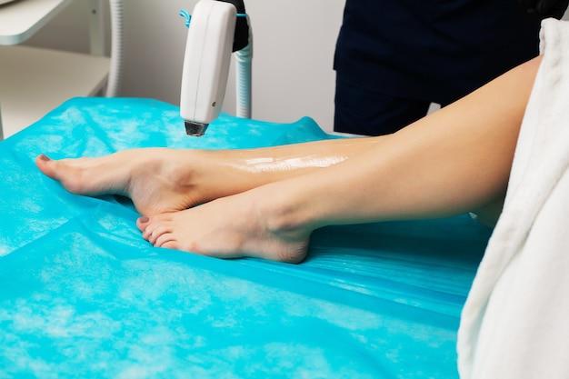 Młoda kobieta odbiera depilację laserową w centrum urody.