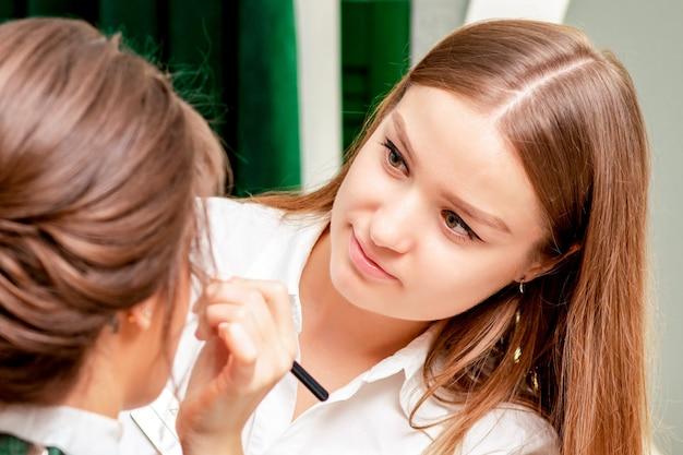 Młoda kobieta odbiera makijaż i fryzurę przez profesjonalnego wizażystę i fryzjera w salonie piękności.