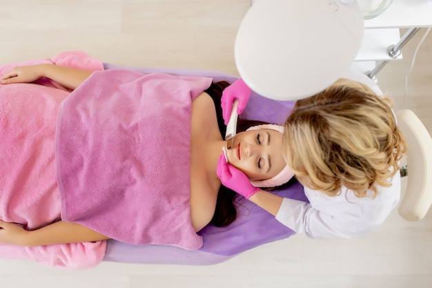 Młoda kobieta odbiera oczyszczanie twarzy peeling kawitacyjny ultradźwiękami