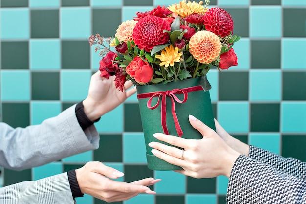 Młoda kobieta odbiera piękne kwiaty piwonii od kobiety dostawy.