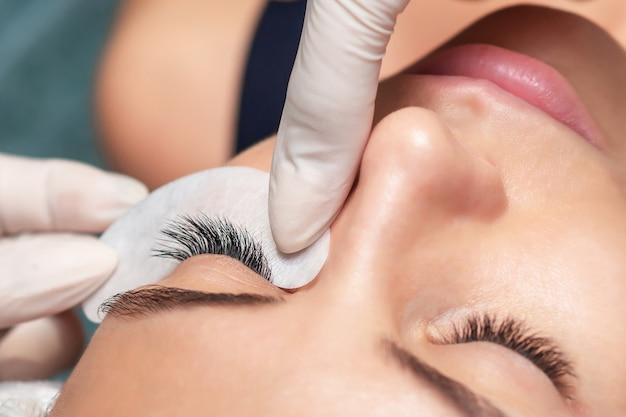 Młoda kobieta odbiera przedłużanie rzęs w gabinecie kosmetycznym, z bliska, procedura przedłużania rzęs