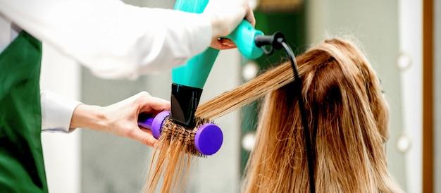Młoda kobieta odbiera suszenie włosów