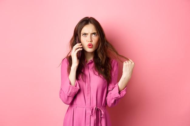 Młoda kobieta odbiera telefon, wygląda na zdezorientowaną i niezdecydowaną, robi zamówienie na wynos na smartfonie, stojąc przed różową ścianą.