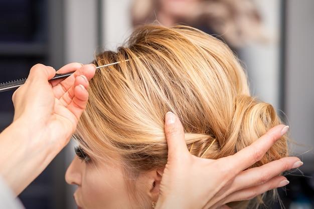 Młoda kobieta odbiera włosy w salonie piękności
