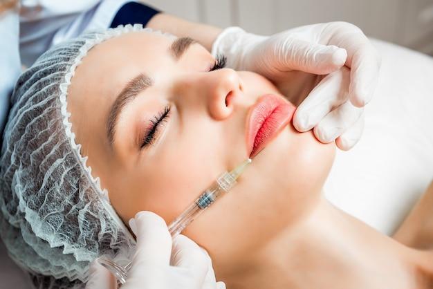 Młoda kobieta odbiera zastrzyk chirurgii plastycznej na jej twarzy z bliska