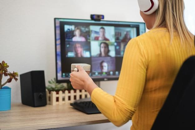 Młoda kobieta odbywa spotkanie dyskusyjne w rozmowie wideo ze swoim zespołem - skoncentruj się na dłoni trzymającej filiżankę kawy