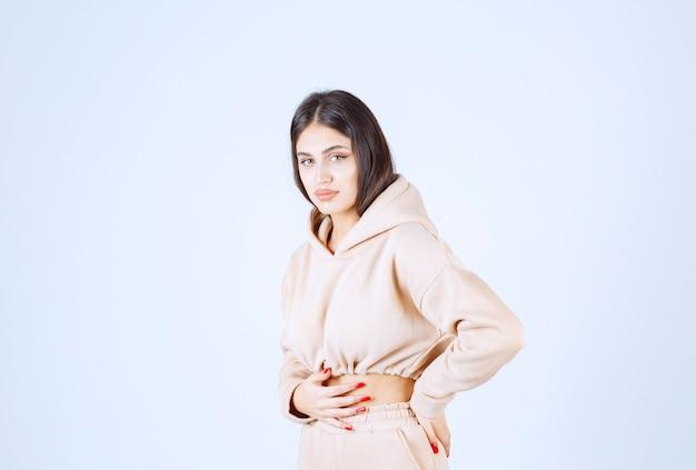 Młoda kobieta odczuwa ból w narządach wewnętrznych