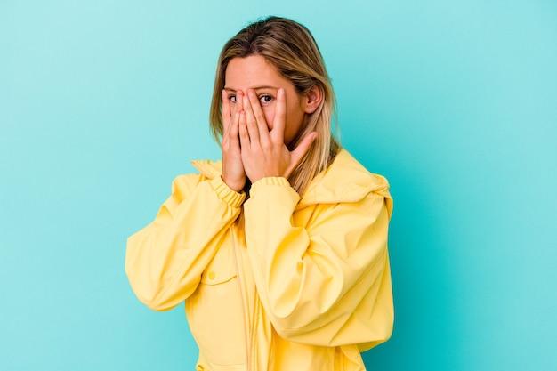 Młoda kobieta odizolowana na niebieskiej ścianie mruga przez palce przestraszona i zdenerwowana