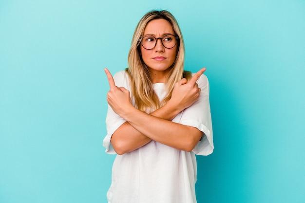 Młoda kobieta, odizolowana na niebieskiej ścianie wskazuje na boki, próbuje wybrać jedną z dwóch opcji