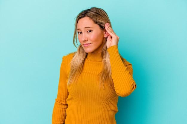 Młoda Kobieta Odizolowana Na Niebieskiej ścianie Zakrywającej Uszy Palcami, Zestresowana I Zdesperowana Głośnym Otoczeniem Premium Zdjęcia