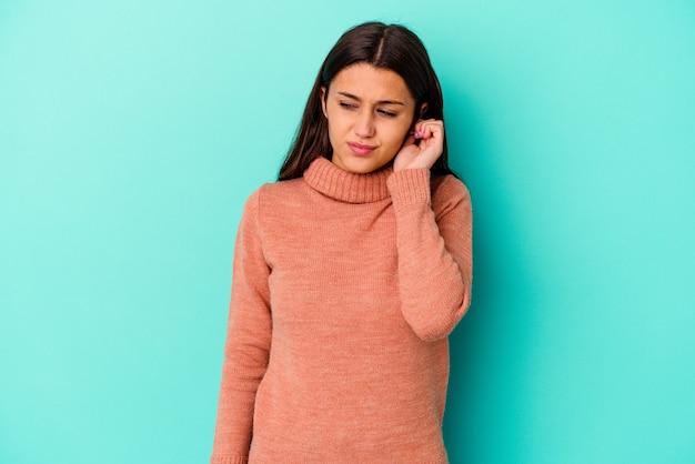 Młoda kobieta odizolowana na niebieskiej ścianie zakrywającej uszy palcami, zestresowana i zdesperowana głośnym otoczeniem