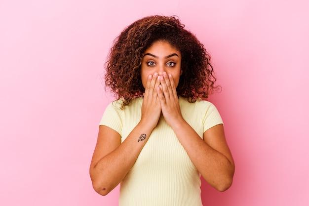 Młoda kobieta odizolowana na różowej ścianie wstrząśnięta, zakrywająca usta rękami, pragnąca odkryć coś nowego