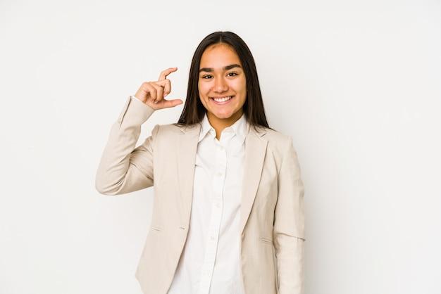 Młoda kobieta odizolowywająca na białej ścianie trzyma coś trochę z palcami wskazującymi, uśmiechnięta i ufna.