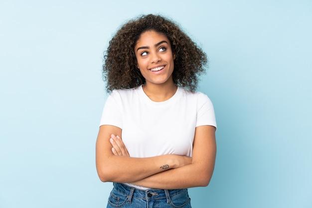 Młoda kobieta odizolowywająca na błękit ścianie przyglądającej up podczas gdy ono uśmiecha się