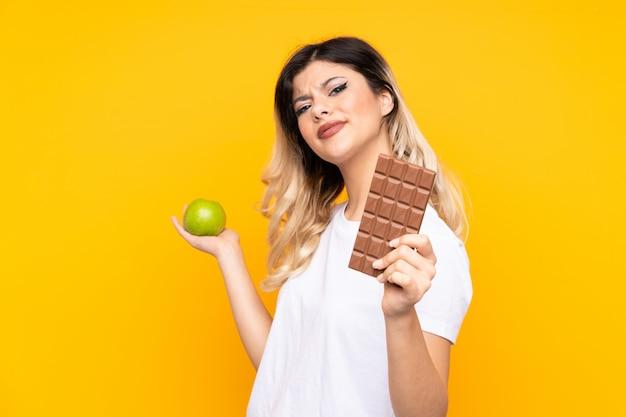 Młoda kobieta odizolowywająca na kolor żółty ścianie ma wątpliwości podczas gdy brać czekoladową pastylkę w jednej ręce i jabłko w drugiej