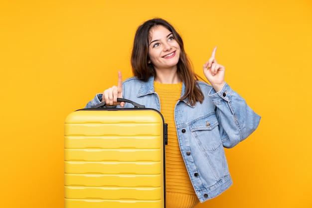 Młoda kobieta odizolowywająca na kolorze żółtym w wakacje z podróży walizką i wskazywać up