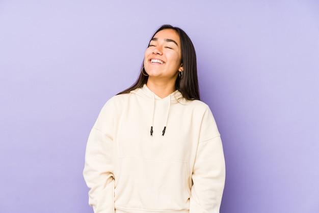 Młoda kobieta odizolowywająca na purpurowej ścianie zrelaksowana i szczęśliwa śmia się, szyja rozciągnięta pokazuje zęby.