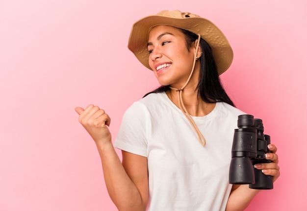 Młoda kobieta odkrywca rasy mieszanej trzymając lornetkę na białym tle na różowym tle punktów z palcem od kciuka, śmiejąc się i beztrosko.