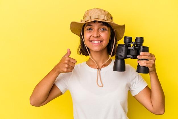 Młoda kobieta odkrywca rasy mieszanej trzymająca lornetkę na żółtym tle, uśmiechnięta i unosząca kciuk w górę