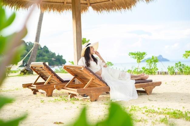 Młoda kobieta odpoczywa i siedzi na leżaku patrząc na piękną plażę w wakacje