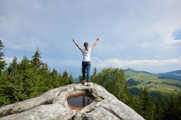 Młoda kobieta odpoczywa na dużym kamieniu w letnim dniu w karpackich górach