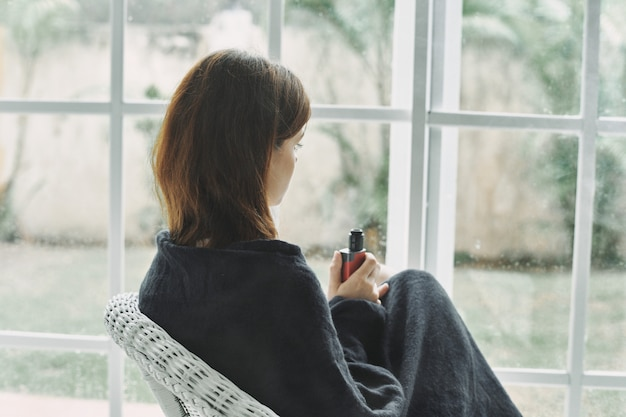 Młoda kobieta odpoczywa na karle w domu okno