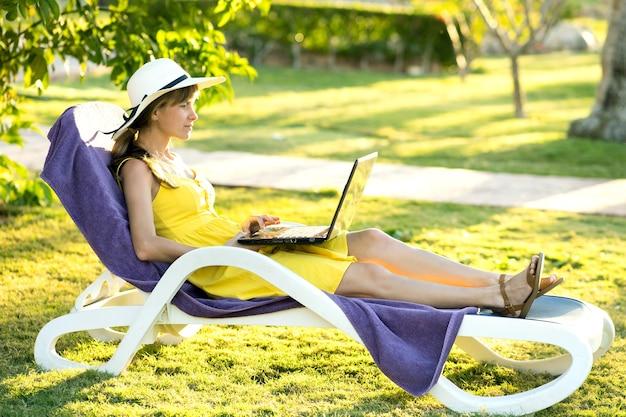 Młoda kobieta odpoczywa na krześle na zielonej trawie trawniku pracuje na komputerze laptop podłączony do bezprzewodowego internetu w letnim parku. prowadzenie biznesu i nauka zdalnie podczas kwarantanny na koncepcji wakacji.