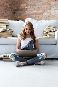 Młoda kobieta odpoczywa na leżance z laptopem i mnóstwo książkami