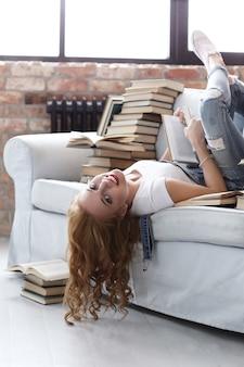 Młoda kobieta odpoczywa na leżance z mnóstwo książkami