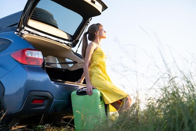 Młoda kobieta odpoczywa na zielonej walizce w pobliżu jej samochodu w lato natura. koncepcja podróży i wakacji.