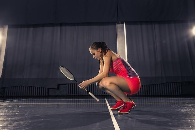 Młoda kobieta odpoczywa po bawić się badminton przy gym