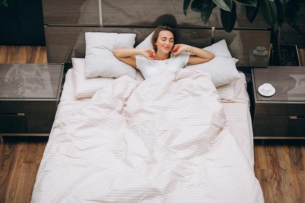 Młoda kobieta odpoczywa w łóżku w ranku