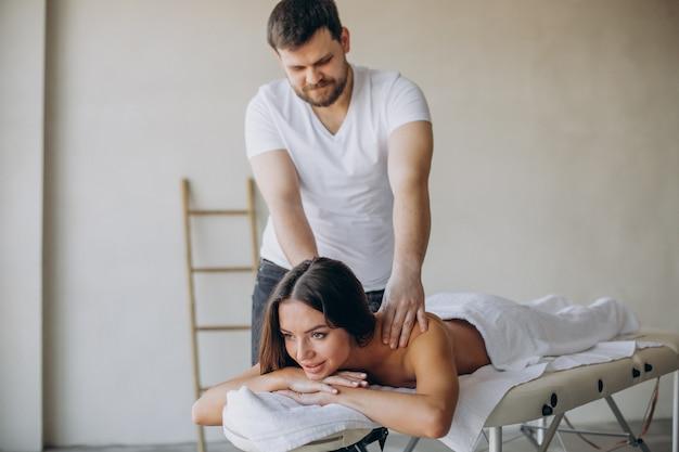 Młoda kobieta odwiedza masażystę w centrum spa