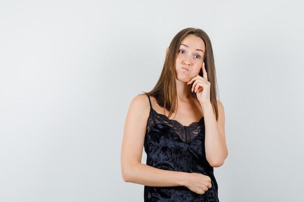 Młoda kobieta odwracając wzrok w czarnym podkoszulku i patrząc niepewnie.