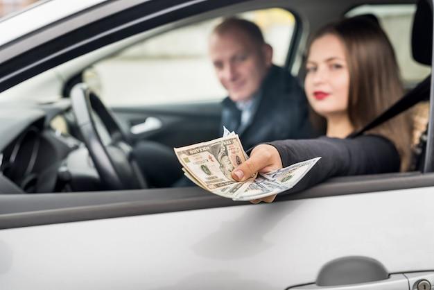 Młoda kobieta oferuje dolarów przez okno samochodu