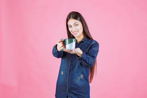 Młoda kobieta oferuje przyjacielowi filiżankę kawy