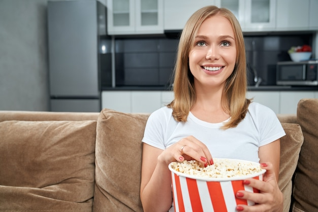Młoda kobieta ogląda film i je popcorn w domu