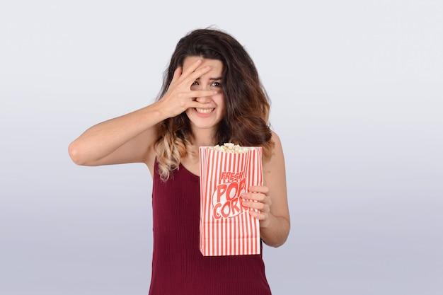 Młoda kobieta ogląda film i je popkorn