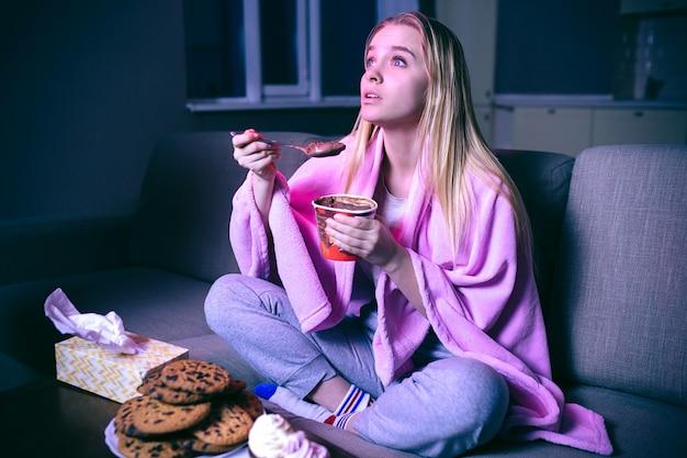 Młoda kobieta ogląda film w nocy. jedzenie lodów lub czekolady z łyżeczką. ciasteczka na stole. transmisja strumieniowa w telewizji.
