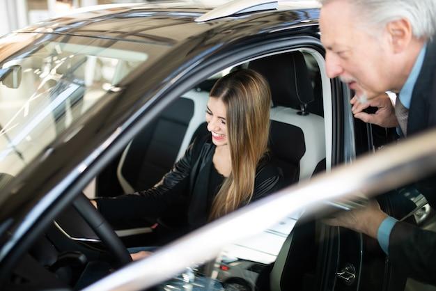 Młoda kobieta ogląda nowy samochód w salonie, podczas gdy dealer wyjaśnia jego cechy