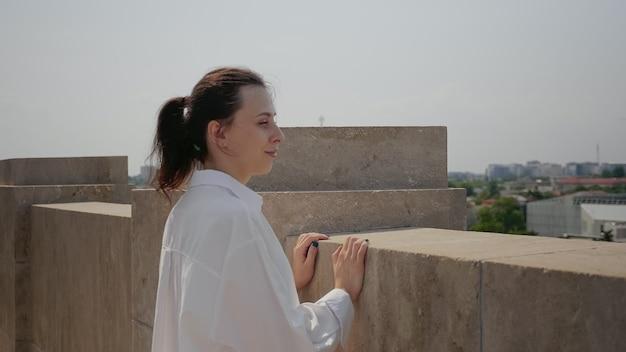 Młoda kobieta ogląda panoramę miasta z punktu obserwacyjnego