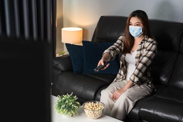 Młoda kobieta ogląda telewizję na kanapie i nosi maskę medyczną w celu ochrony koronawirusa (covid-19)