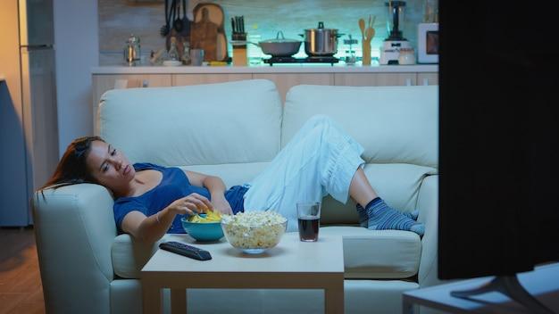 Młoda kobieta oglądając telewizję i nudząc się, siedząc na kanapie w salonie w domu. zmęczona, wyczerpana, samotna pani relaksuje się przed telewizorem leżąc na wygodnej sofie jedząc przekąski późno w nocy