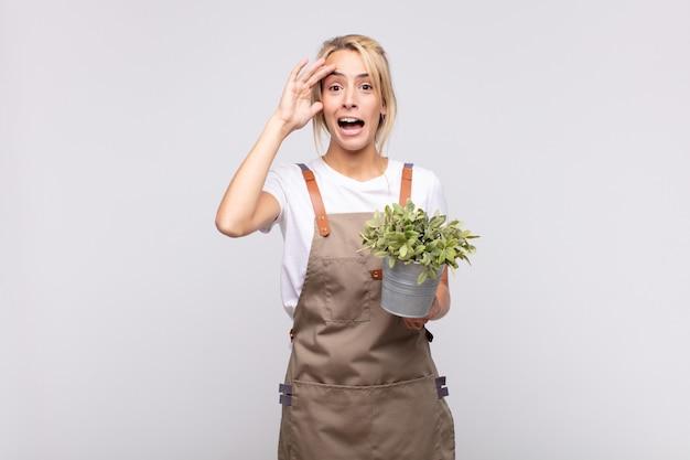 Młoda kobieta ogrodniczka wyglądająca na szczęśliwą, zdziwioną i zaskoczoną, uśmiechniętą i uświadamiającą sobie niesamowite i niewiarygodnie dobre wieści